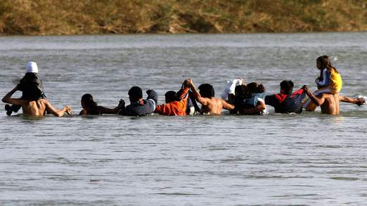 Citizens of Mexico, dangerously and illegally, attempt to cross the Rio Grande into South Texas.